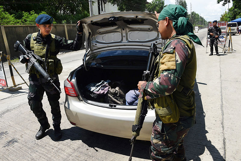 Policemen inspect a vehicle's trunk at a checkpoint in Iligan City in May 2017. AFP, file