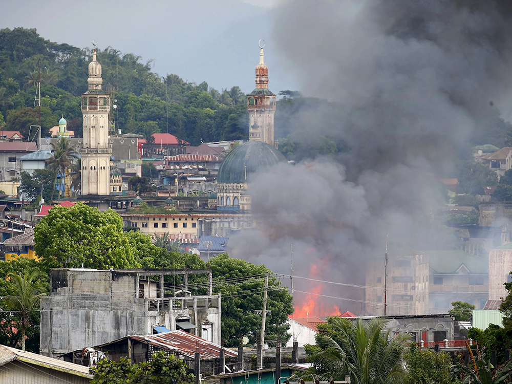 A fire rages at houses following airstrikes by Philippine Air Force in Marawi, southern Philippines, Saturday, May 27, 2017. Philippine military jets fired rockets at militant positions Saturday as soldiers fought to wrest control of the southern city from gunmen linked to the Islamic State group. AP/Bullit Marquez