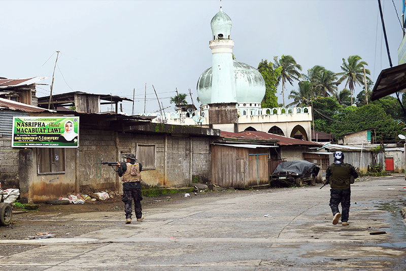 Government troops patrol a deserted street in Marawi City as planes and helicopters bombed positions of Maute fighters yesterday. Civilians waved white flags from their windows to show they were not combatants as soldiers fought to wrest control of the city from gunmen linked to the Islamic State. AFP