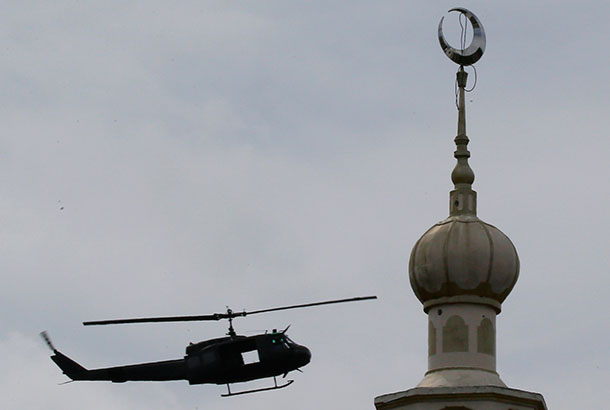 """A military helicopter hovers by a mosque on May 29, 2017 as government troops battle with Muslim militants who continue to hold their ground in some areas of Marawi. The military has declared a """"humanitarian pause"""" in operations for Eid'l Fitr. AP Photo/Bullit Marquez, file"""