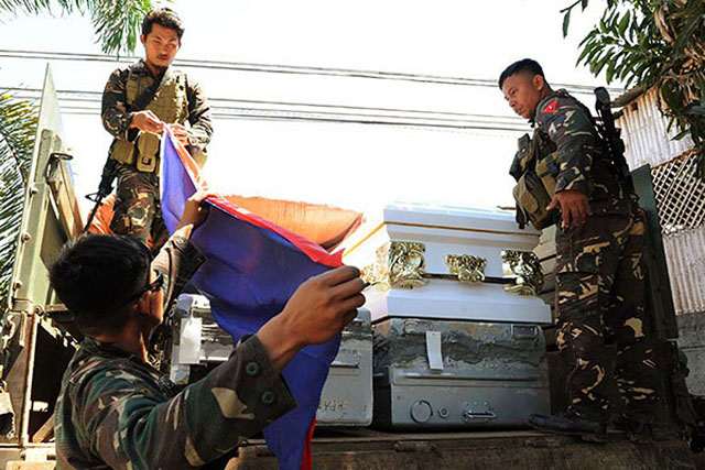 Flags are draped on the caskets of 13 Marines in Iligan City before ...