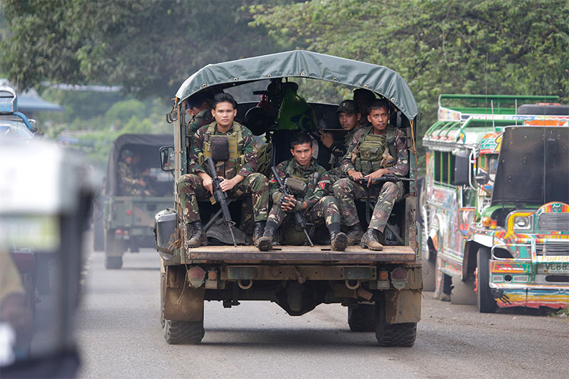 In this June 9, 2017, photo, soldiers ride a military vehicle on the outskirts of Marawi city, southern Philippines. The Philippine military says 13 marines have been killed in fierce fighting with Muslim militants who have laid siege to southern Marawi city. AP/Aaron Favila
