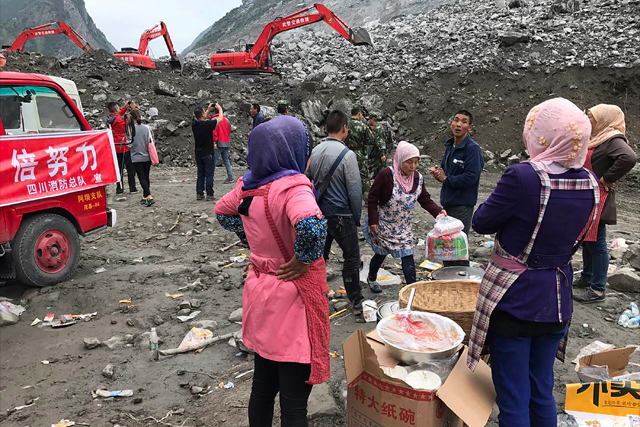 Women watch as earthmoving equipment digs at the site of a landslide in Xinmo village in Maoxian County in southwestern China's Sichuan Province, Sunday, June 25, 2017. Crews searching through the rubble left by a landslide that buried a mountain village under tons of soil and rocks in southwestern China on Saturday found bodies, but more than 100 people remained missing. AP / Ng Han Guan