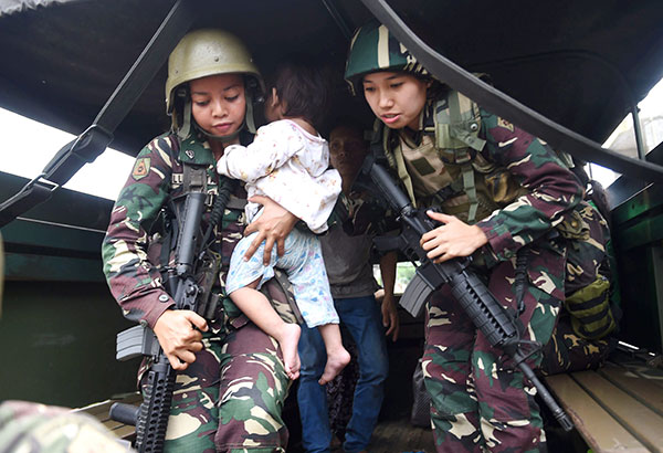 A soldier holds a child rescued from the battle zone in Marawi City on Sunday. AFP
