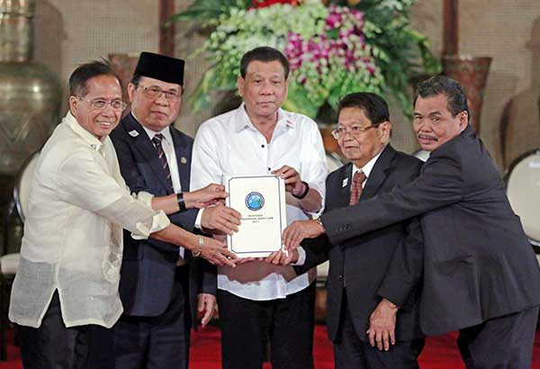 President Duterte holds the draft of the Bangsamoro Basic Law during a turnover ceremony at Malacañang on May 17. File photo