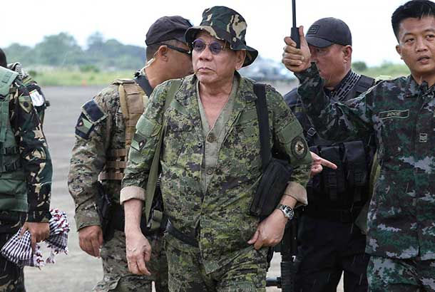 In this July 20 photo, President Rodrigo Duterte, center, clad in a camouflage uniform prepares to board a helicopter from an undisclosed place to visit troops in Marawi city. Second from right is Armed Forces Chief Gen. Eduardo Año.Presidential Photographers Division/Ace Morandante, file