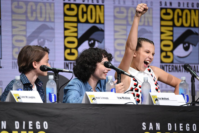 """Millie Bobby Brown, right, gestures as from left, Noah Schnapp, and Finn Wolfhard look on at the """"Stranger Things"""" panel on day three of Comic-Con International on Saturday, July 22, 2017, in San Diego. Photo by Richard Shotwell/Invision/AP"""