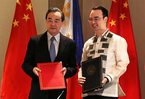 Foreign Affairs Secretary Alan Peter Cayetano (right) and visiting Chinese Foreign Minister Wang Yi pose after a signing ceremony for a memorandum of understanding at the Shangri-La Hotel at the Fort in Taguig City yesterday. EDD GUMBAN