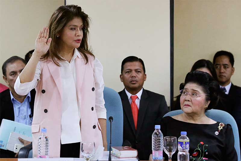 Ilocos Norte Governor Imee Marcos, left, is sworn as her mother Imelda, right, widow of the late strongman Ferdinand Marcos, looks on during a congressional inquiry at the House of Representatives in suburban Quezon city, north of Manila, Philippines on Tuesday July 25, 2017. The inquiry is based on a resolution filed by Majority Leader Rodolfo Farinas asking the Committee on Good Government and Public Accountability to look into the alleged anomalous vehicle purchases of the Ilocos Norte province using the tobacco excise tax fund. Six employees of the provincial government who were cited in contempt and detained for being evasive in their answers during the hearings were also released Tuesday. AP/Aaron Favila