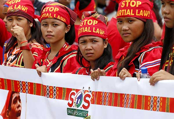 Lumads display a banner as they join a march during President Duterte's SONA on Monday. AP