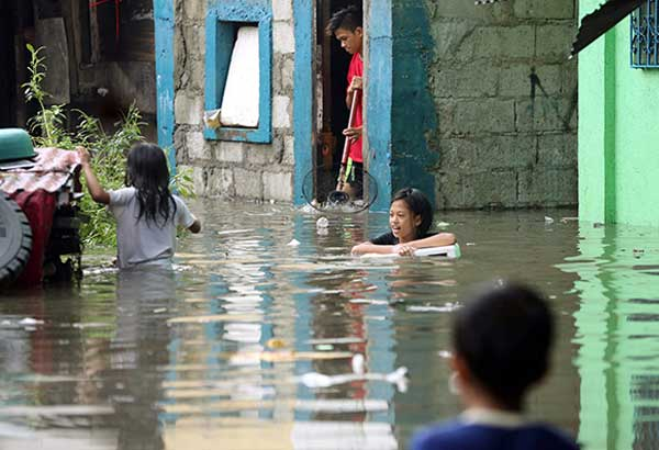 Residents of Barangay Tatalon in Quezon City wade through floodwaters spawned by Tropical Storm Gorio yesterday. BOY SANTOS