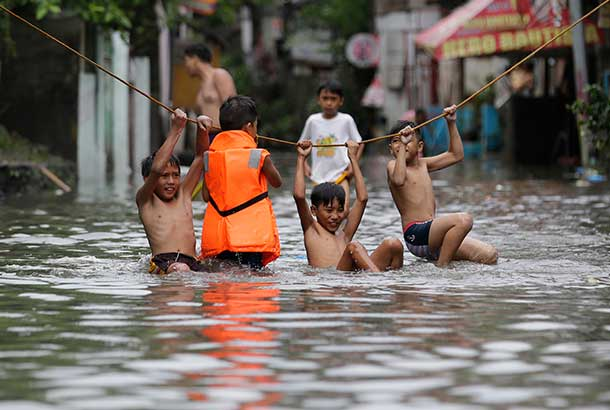In this July 27, 2017photo, boys play outside their flooded homes after heavy rains from Tropical Storm Gorio flooded parts of Metro Manila. Strong rains caused floods in low-lying areas and classes were suspended in most schools in the capital.AP Photo/Aaron Favila, File