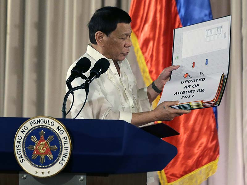 Philippine President Rodrigo Duterte shows documents containing a list of suspected drug dealers and users during the 19th Founding Anniversary of the Volunteers Against Crime and Corruption at the Malacanang Presidential Palace in Manila, Philippines on Wednesday, Aug. 16, 2017. AP/Aaron Favila