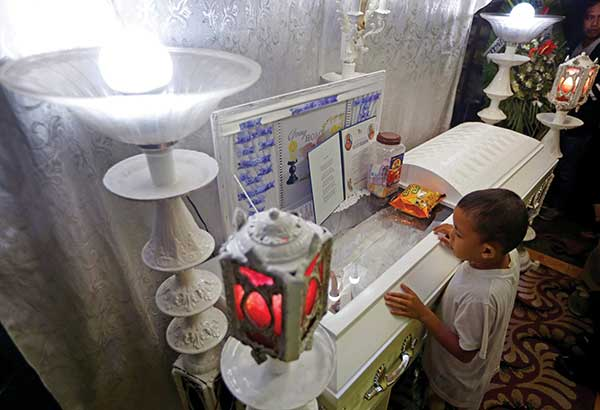 A neighbor and friend of slain student Kian Loyd delos Santos refuses to leave his wake in Caloocan City yesterday. AP