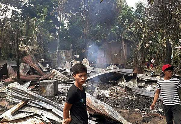 Residents stand near razed houses in Barangay Tubigan in Maluso, Basilan following an attack by Abu Sayyaf bandits yesterday. JOHN UNSON