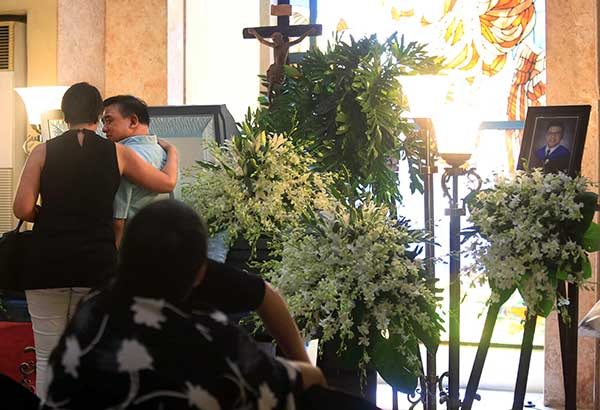 Horacio Castillo II, father of slain UST law student Horacio III, is consoled by a visitor during the wake at the Santuario de San Antonio in Makati. File
