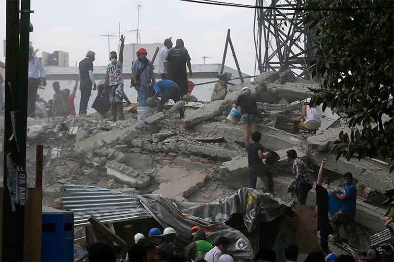 Volunteers search a building that collapsed after an earthquake, in the Roma neighborhood of Mexico City, Tuesday, Sept. 19, 2017. A magnitude 7.1 earthquake has rocked central Mexico, killing at least 55 people as buildings collapsed in plumes of dust and thousands fled into the streets in panic. AP/Eduardo Verdugo