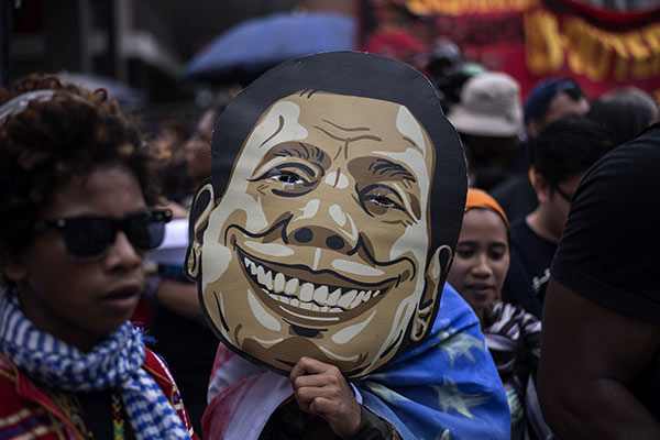 An activist holds a Duterte mask during a protest against Philippine President Rodrigo Duterte near the Malacanang palace in Manila on September 21, 2017. Activists are holding a series of protests on September 21 to denounce drug war killings and what they say is a slide to tyranny under Philippine President Rodrigo Duterte. Noel Celis/AFP