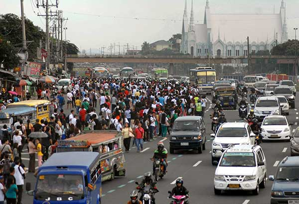 Commuters spill over several lanes on Commonwealth Avenue in Quezon City as a transport strike limited the number of jeepneys plying routes in Metro Manila yesterday. BOY SANTOS