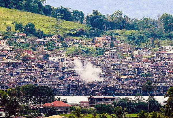 Smoke billows from destroyed buildings after government troops fired mortars at a Maute position in Marawi. The military said the fighting would end 'very soon.' AFP, File