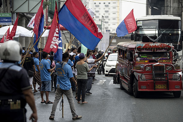 Activists and jeepney drivers hold banners during a jeepney transport strike held in Manila on October 16, 2017. Jeepney drivers and activists staged a nationwide transport strike in protest against the government's plan to phase out the ubiquitous passenger jeepney as part of a modernization campaign to turn the Philippines' main form of public transport green. Noel Celis/AFP