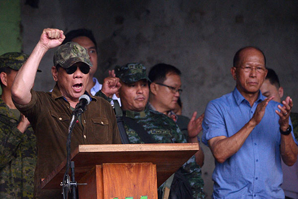 """Philippines President Rodrigo Duterte (L) raises a clenched fist, as he shouts declaring Marawi """"liberated"""" during a ceremony inside the battle area of Bangolo district in Marawi on October 17, 2017. Philippine President Rodrigo Duterte on October 17 declared a southern city """"liberated from terrorists' influence"""" but the military said the five-month battle against militants loyal to the Islamic State group was not yet over. Ted Aljibe/AFP"""