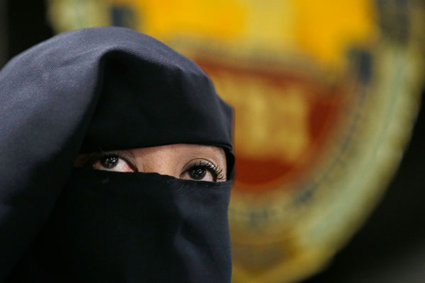Wearing a burqa, Karen Aizha Hamidon, the widow of the leader of a militant band allegedly sympathetic to the Islamic State group, is presented to reporters during a news conference at the National Bureau of Investigation in Manila, Philippines, on Wednesday, Oct. 18, 2017. Authorities said she recruited foreign fighters to the country and spread extremist propaganda. AP Photo/Aaron Favila