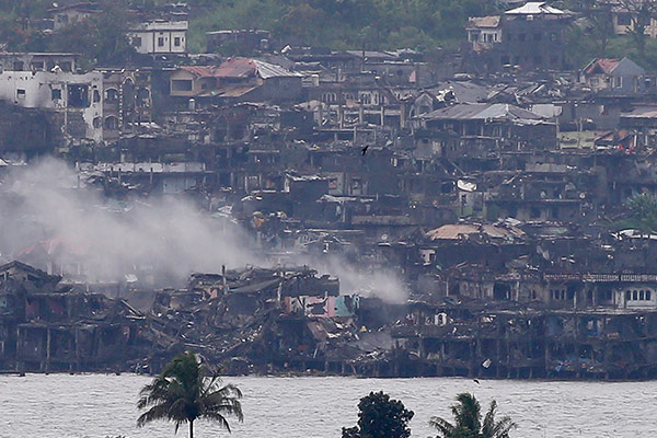 Smoke rises from the city as explosions continue to reverberate in Marawi, a day after President Rodrigo Duterte declared its liberation in the southern Philippines, Wednesday, Oct. 18, 2017. Sporadic explosions and gunfire continue Wednesday as Philippine soldiers fought to gain control of the last pocket of Marawi controlled by Islamic militants. AP Photo/Bullit Marquez