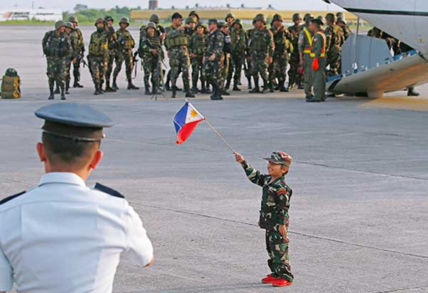 Johan Peralta waves a Philippine flag as troops, one of the first battalions to be deployed to Marawi, arrive to a hero's welcome at Villamor Air Base in Pasay City yesterday. AP