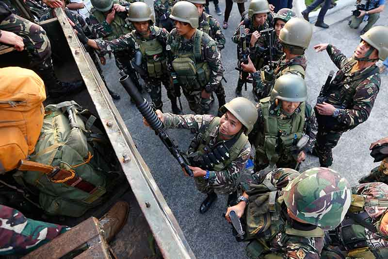 One of the military first battalions to be deployed in the besieged southern city of Marawi board a military truck as they arrive to a hero's welcome at Villamor Air Base Friday, Oct. 20, 2017, in Pasay city, southeast of Manila, Philippines. The military has begun to scale down their forces in Marawi after President Rodrigo Duterte declared its liberation following the killings of the militant leaders after five months of military offensive. AP/Bullit Marquez