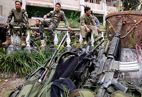 Firearms and battle gear are seen on the ground as soldiers take a break in Bangolo, Marawi City hours after combat operations were declared terminated yesterday. KRIZJOHN ROSALES