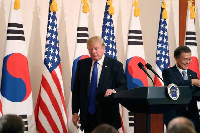 """President Donald Trump, left, leaves a joint news conference with South Korean President Moon Jae-in, right, at the Blue House in Seoul, South Korea, Tuesday, Nov. 7, 2017. President Trump, on his first day on the Korean peninsula, signaled a willingness to negotiate with North Korea to end its nuclear weapons program, urging Pyongyang to """"come to the table"""" and """"make a deal."""" AP Photo/Andrew Harnik"""