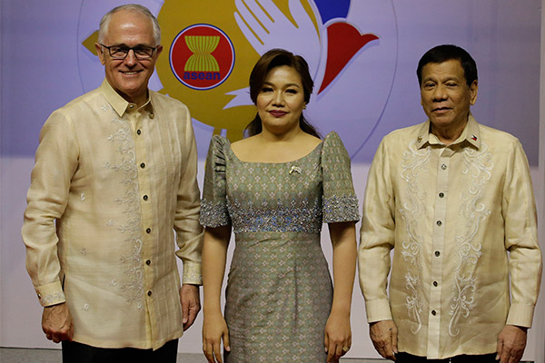Philippine President Rodrigo Duterte, right, and his partner Cielito Avancena, center, poses with Australian Prime Minister Malcolm Turnbull, left, before the start of the Special Gala Celebration of the 50th Anniversary of ASEAN in Manila, Philippines on Sunday, Nov. 12, 2017. AP Photo/Aaron Favila-POOL
