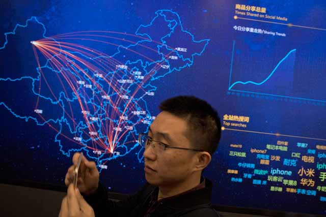 """A visitor to the command center for Chinese e-commerce giant JD.com stands near a digital map showing the flow of deliveries across the country in Beijing, China, Saturday, Nov. 11, 2017. Chinese consumers are spending billions of dollars shopping online for anything from diapers to diamonds on """"Singles Day,"""" a day of promotions that has grown into the world's biggest e-commerce event. AP/Ng Han Guan"""