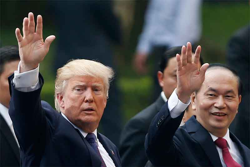 US President Donald Trump, left, and Vietnam's President Tran Dai Quang wave their hands after a press conference at the Presidential Palace in Hanoi, Vietnam Sunday, Nov. 12, 2017. Kham/Pool Photo via AP