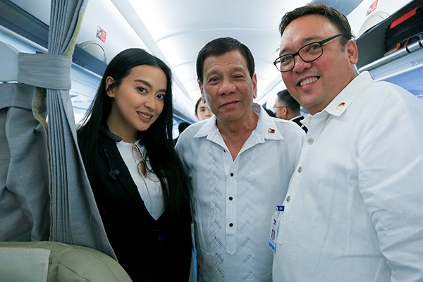 "President Rodrigo Duterte poses for a photo with Presidential Communications Assistant Secretary Margaux ""Mocha"" Uson and Presidential spokesperson Harry Roque while on board the Philippine Airlines chartered flight prior to their departure for Vietnam on Nov. 8, 2017. Albert Alcain/Presidential Photo, File"