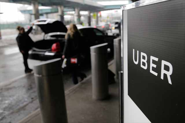 In this March 15, 2017, file photo, a sign marks a pick-up point for the Uber car service at LaGuardia Airport in New York. Uber is coming clean about its cover-up of a year-old hacking attack that stole personal information about more than 57 million of the beleaguered ride-hailing service's customers and drivers. The revelation Tuesday marks the latest stain on Uber's reputation. AP/Seth Wenig, File