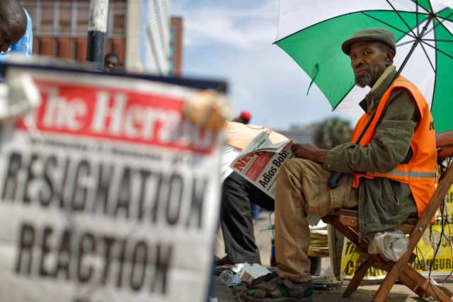 Zimbabweans read morning newspapers Wednesday, Nov. 22, 2017, a day after President Robert Mugabe resigned, at a news stand in downtown Harare, Zimbabwe. Mugabe resigned as president with immediate effect Tuesday after 37 years in power, shortly after parliament began impeachment proceedings against him. AP/Ben Curtis