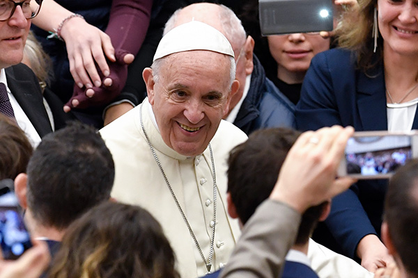 Pope Francis smiles as people greet him upon his arrival for his weekly general audience at the Aula Paolo VI on December 27, 2017 in Vatican. Andreas Solaro/AFP