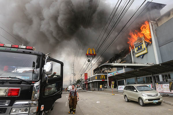 This photo taken on Dec. 23, 2017 shows a firefighter standing in front of a burning shopping mall in Davao City on the southern Philippine island of Mindanao. Thirty-eight people were killed in a fire that engulfed a shopping mall in the southern Philippine city of Davao, local authorities said on December 24.Manman Dejeto/AFP