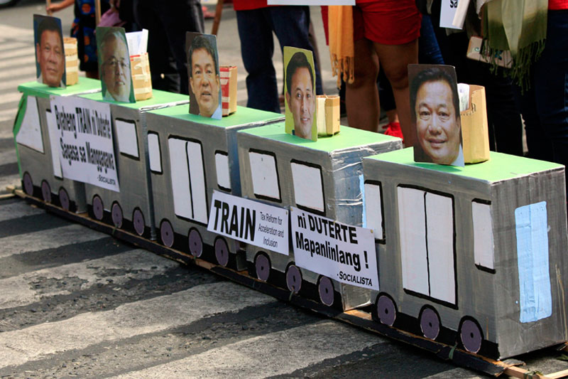 Militant labor groups stage a protest against the TRAIN law in Mendiola, Manila yesterday. Edd Gumban