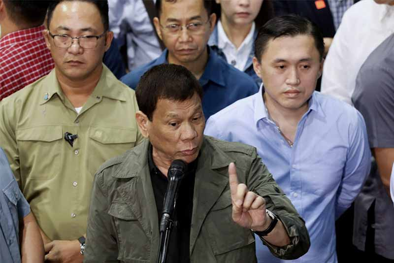 "President Rodrigo Duterte, with presidential aide Christopher ""Bong"" Go next to him, is interviewed on the sidelines of the inauguration of the new Communications, Navigation, Surveillance / Air Traffic Management Systems Development Project at the Philippine Air Traffic Management Center in Pasay City on Jan. 16, 2018. Simeon Celi Jr./Presidential Photo, File"