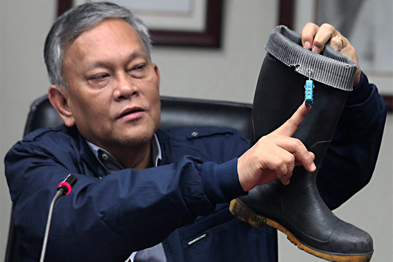 MIAA general manager Ed Monreal shows an expensive padlock attached to a ground handler's boot during a press conference yesterday. A raid on the quarters of ground handlers yielded several boots containing padlocks, jewelry and other small items allegedly taken from the luggage of passengers. Rudy Santos