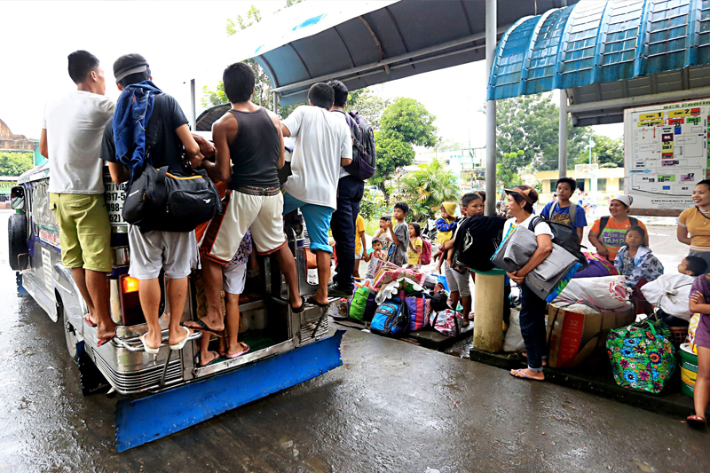 Evacuees from the Bagong Bayan Central School in Legazpi, Albay ride a jeepney yesterday after they were allowed to return to their houses, which were not in the danger zone of Mayon Volcano. Mayon is being monitored for non-explosive eruptions. Edd Gumban