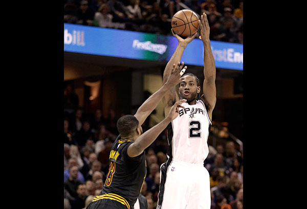 San Antonio Spurs' Kawhi Leonard shoots over Cleveland Cavaliers' Tristan Thompson in the first half of an NBA game, Saturday, in Cleveland. AP