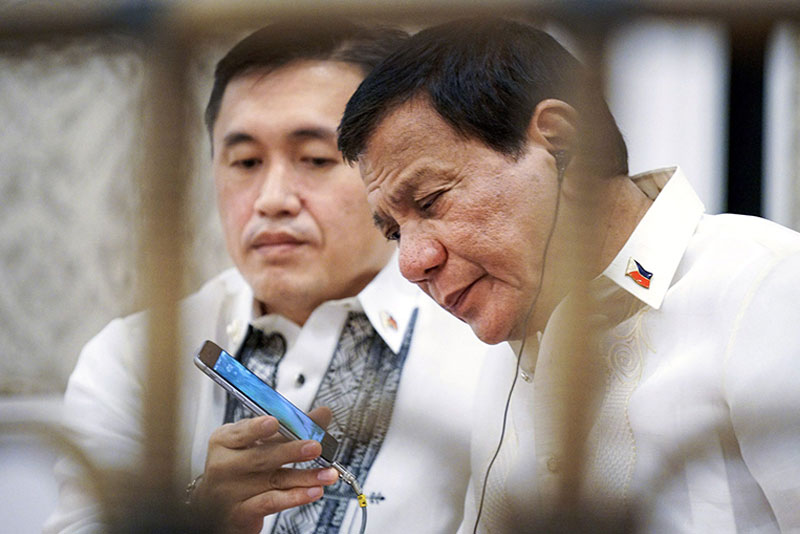 President Duterte takes a call from US President Donald Trump on the sidelines of a gala dinner for leaders of the Association of Southeast Asian Nations at the Sofitel Hotel in Pasay City on Saturday night. Holding the phone for Duterte is presidential assistant Christopher Go.