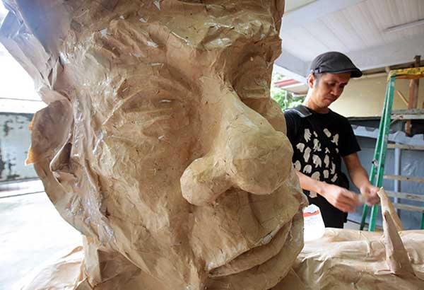 A member of the militant group Bayan Muna prepares an effigy of President Duterte yesterday for the group's protest rallies during the State of the Nation Address today. MICHAEL VARCAS