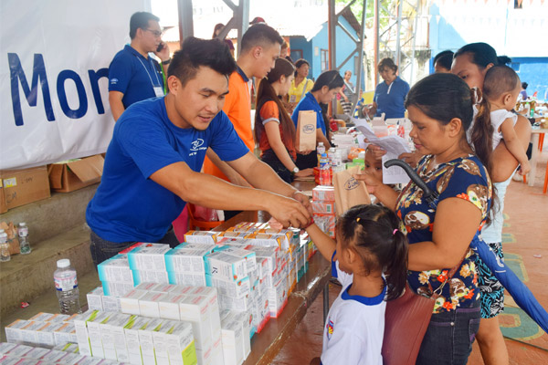 As part of Ford Philippines' Global Caring Month activities, Ford employees and dealer employees distribute prescription medicines to parents and their children of Brgy. Tunasan, Muntinlupa City. Ford Philippines/Released
