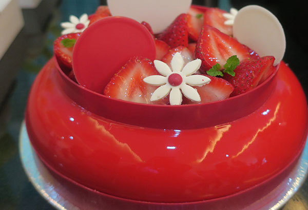 Strawberry field entremet made with a chocolate cake, strawberry compote, white chocolate mousse finished with a shiny red glaze.