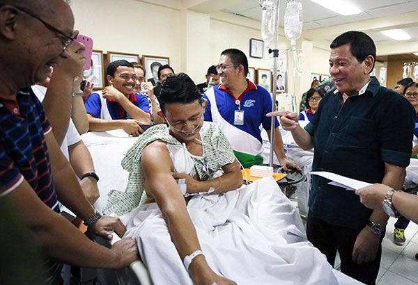 President Duterte shares a light moment with Cpl. Renante Guipitcio during a visit to wounded soldiers and policemen fighting in Marawi at the Adventist Medical Center in Iligan City yesterday.